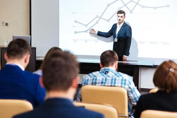 Intelligent speaker standing and lecturing at business conference in boardroom.jpeg